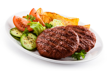 Grilled beefsteaks, baked potatoes and vegetable salad