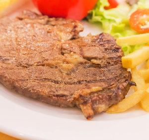 Grilovaný vepřový steak s hranolky a zeleninovou oblohou